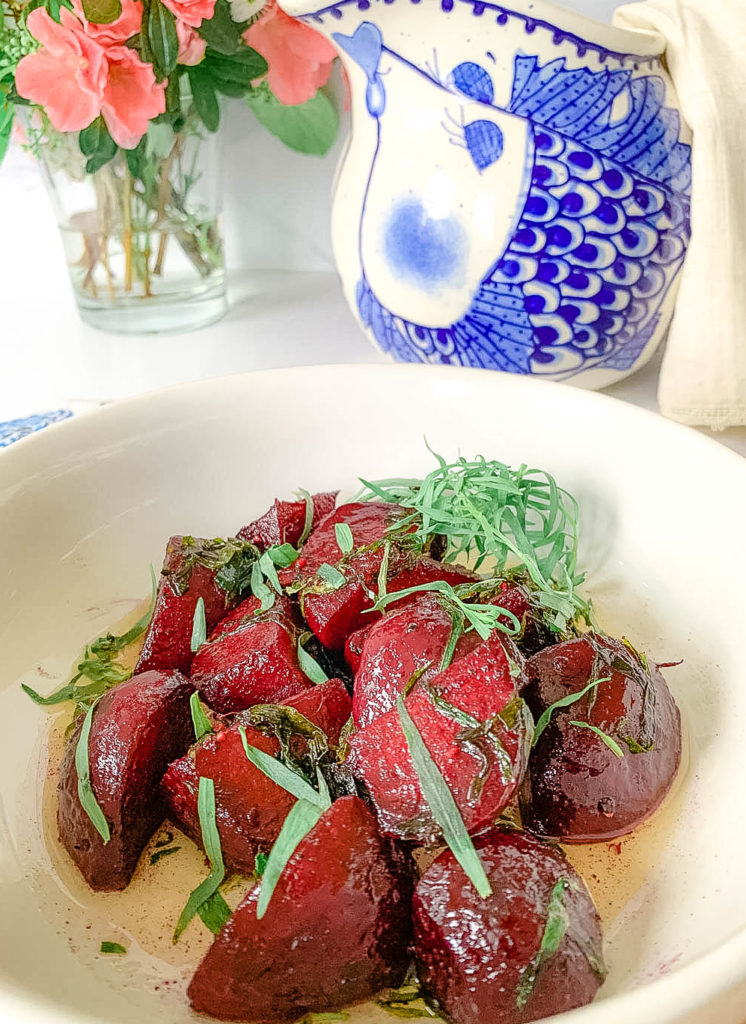 a white bowl with beets and a blue pitcher, with flowers