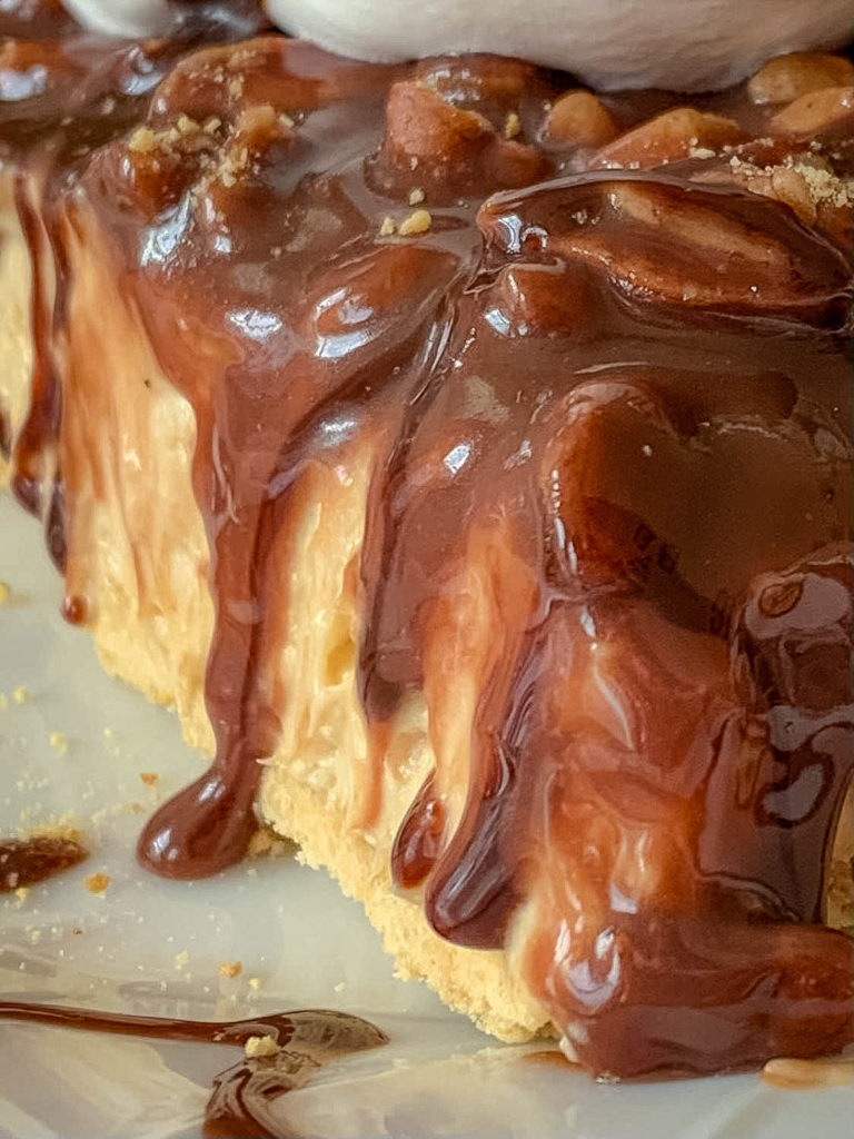 close up of chocolate running down a side of peanut butter pieon white plate