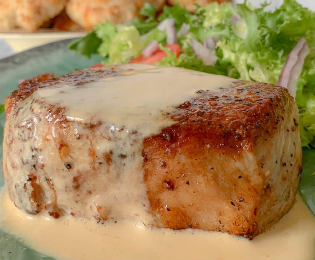 close up of a pork chop with sauce