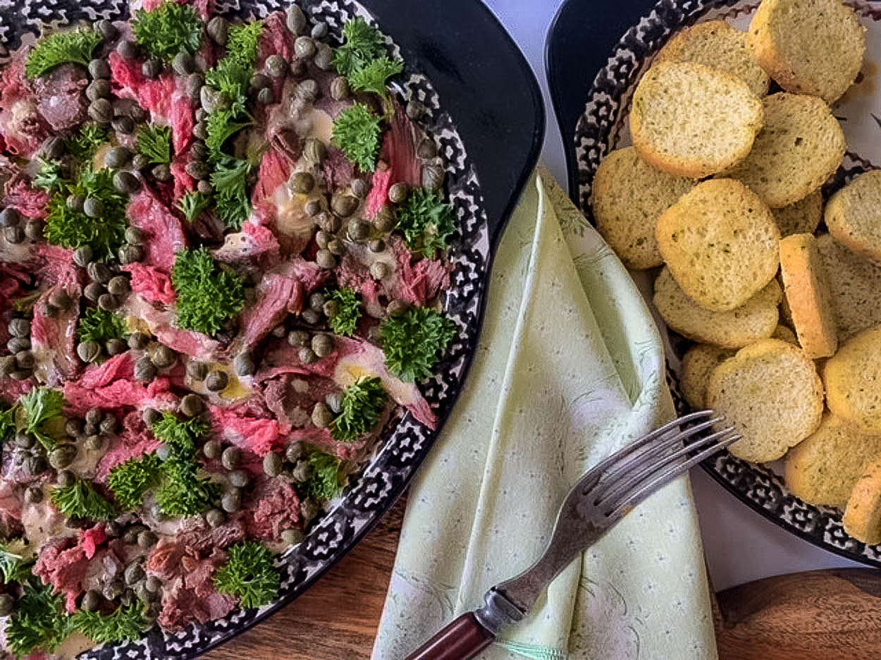overhead picture of beef and parsley and capers on black platter