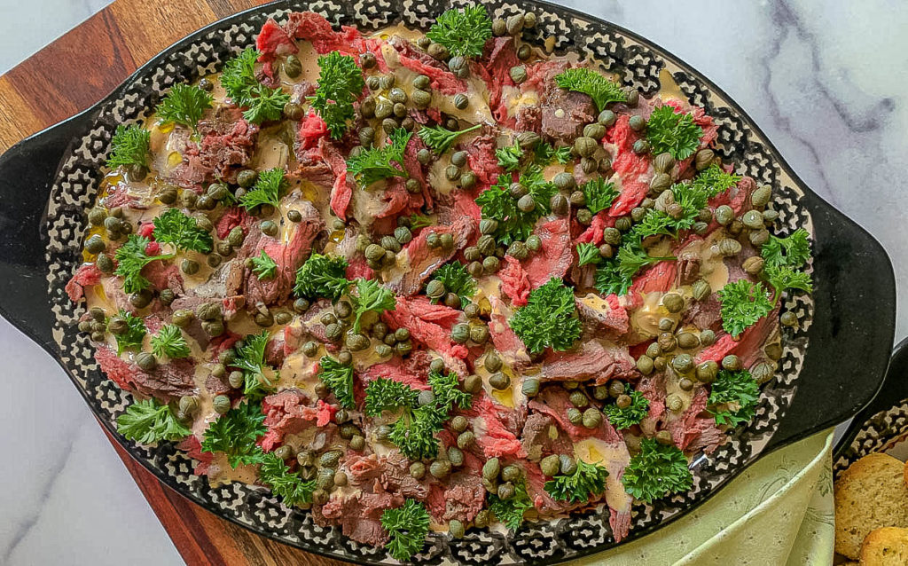 close up picture of beef and parsley and capers on black platter