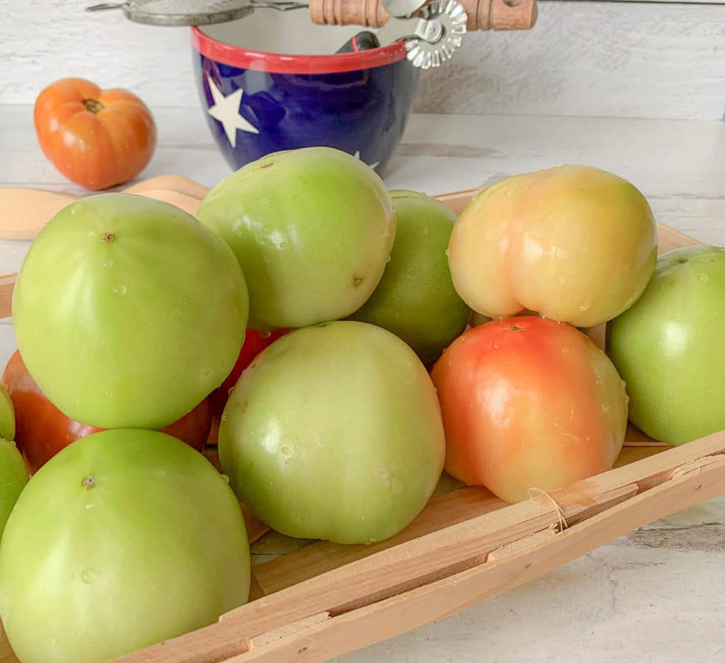 basket of green tomatoes on a counter, with bowl