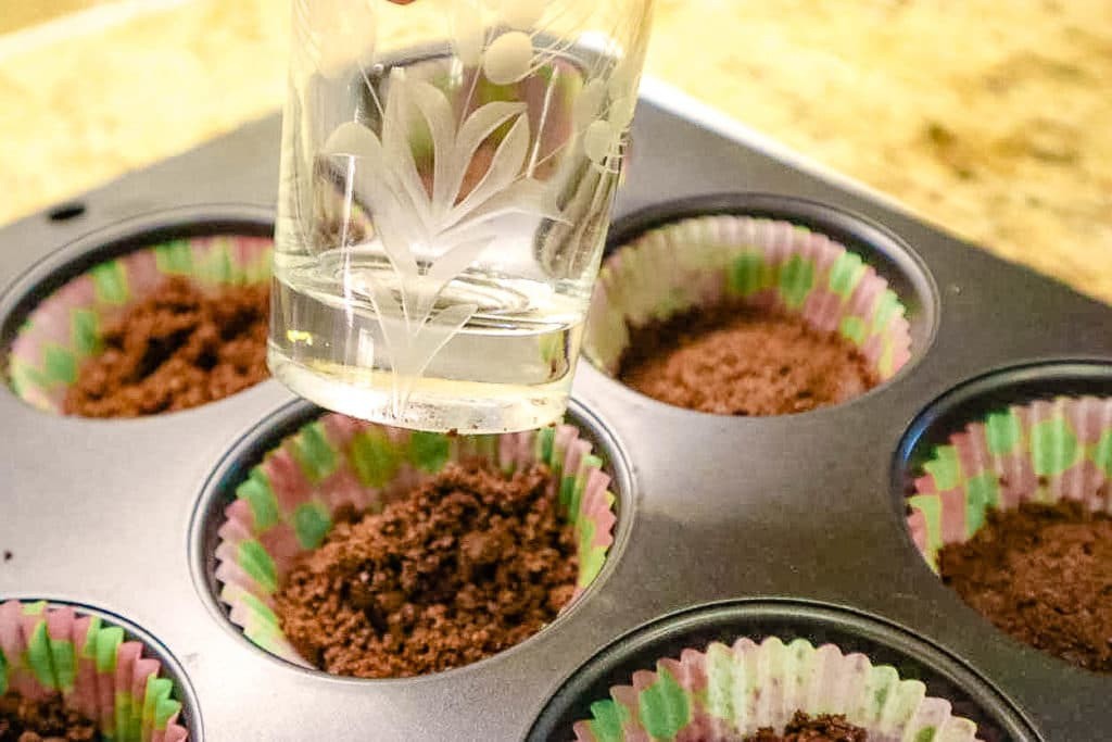 chocolate crumbs being pressed into a muffin tin