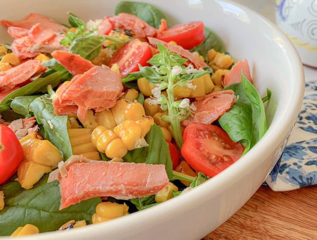 close up of a white bowl with salad, with smoked salmon