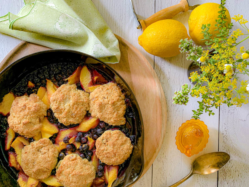 cast iron skillet, with Peach And Blueberry Cobbler With Ginger Biscuits