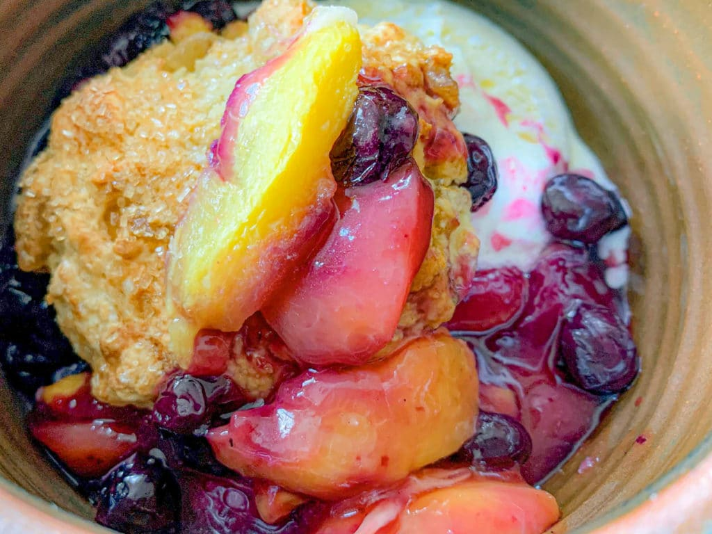 Peach And Blueberry Cobbler With Ginger Biscuits in a bowl