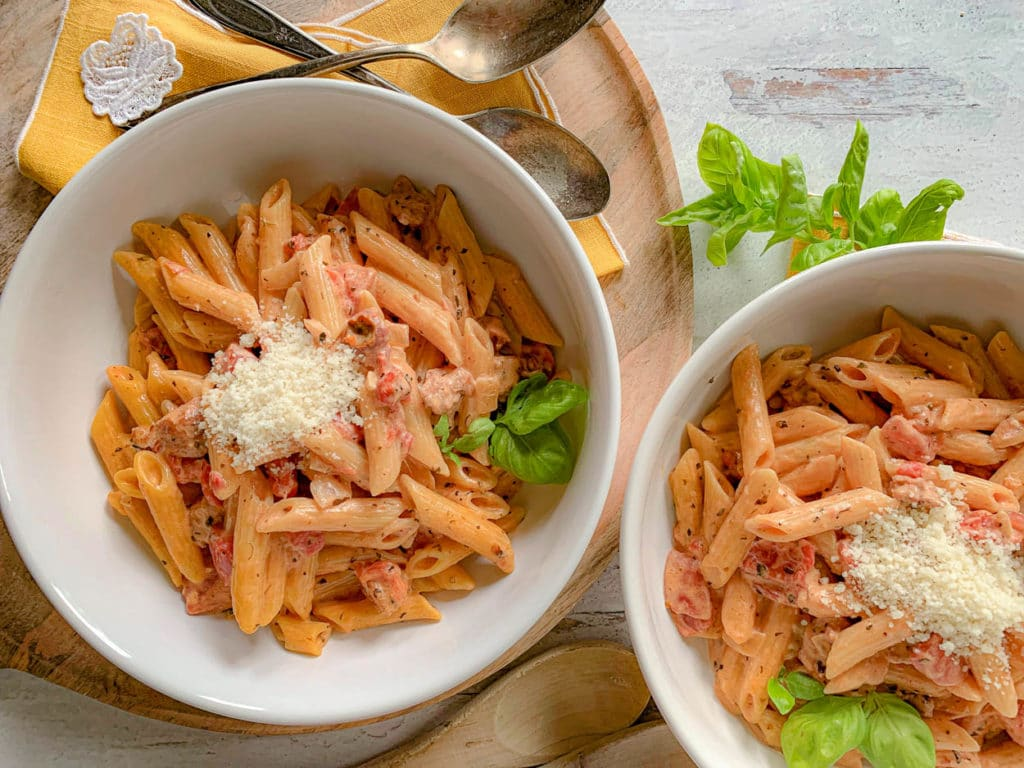2 white bowls, with Creamy Sausage And Tomato Penne