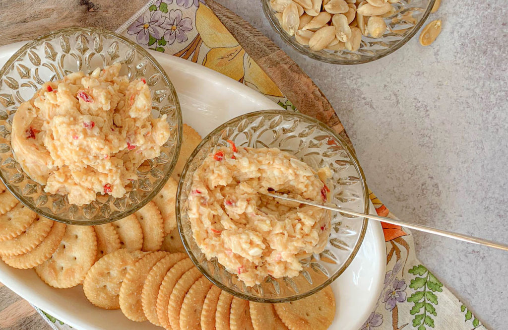a wooden board with crackers, with Piquant White Cheddar Pimento Cheese