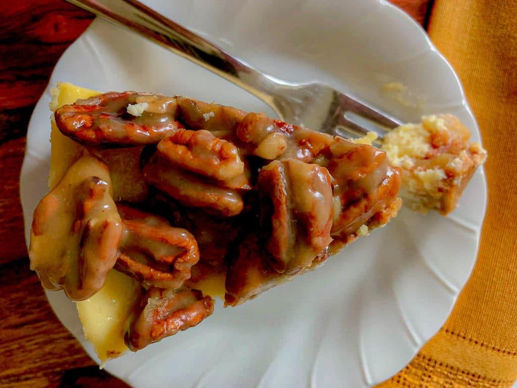 above photo of a slice of Apple Bottom Bourbon Pecan Cheesecake