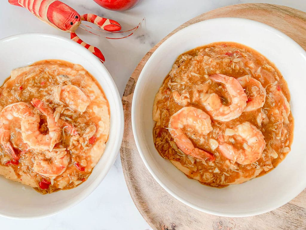 two white bowls of Charleston Shrimp And Grits With Crab Gravy