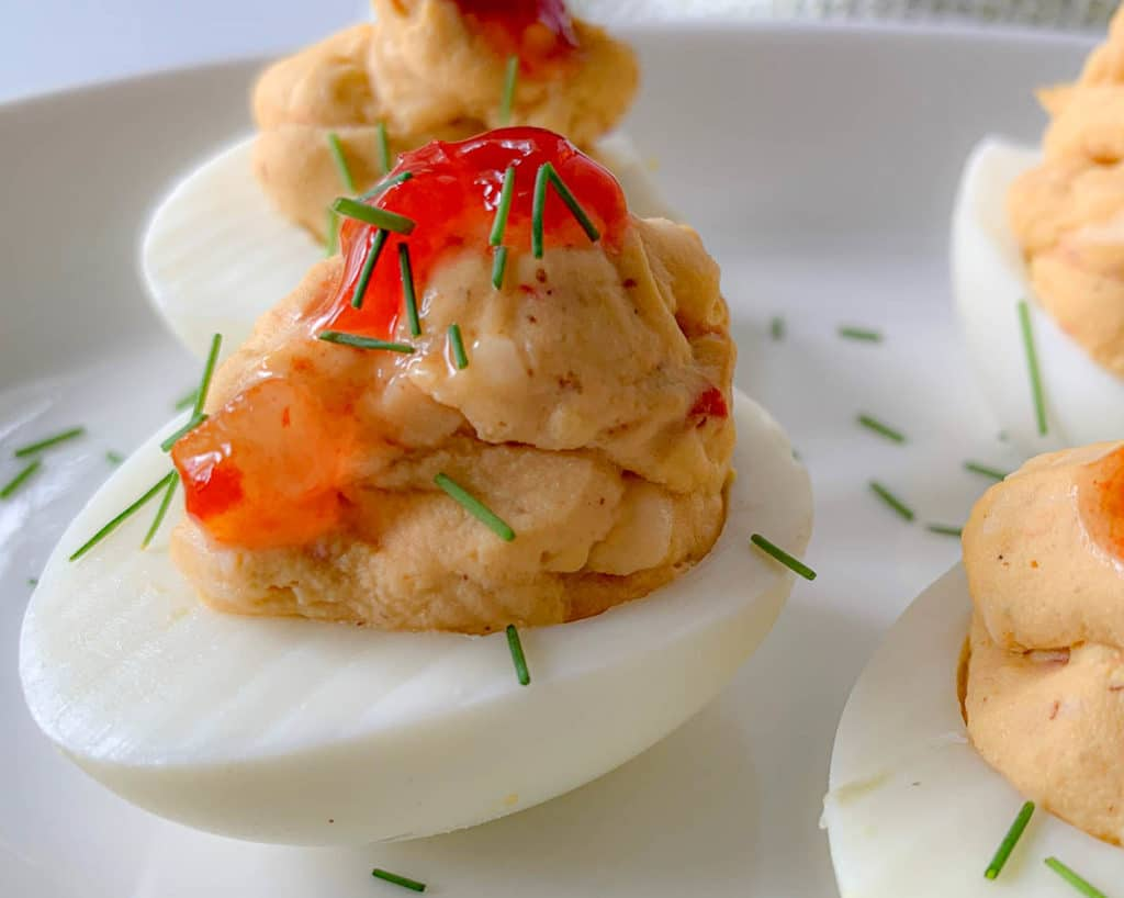 deviled eggs on a white plate, with chives