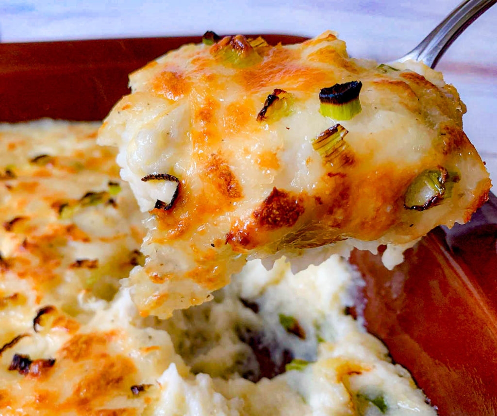 Cheesy Mashed Potatoes Casserole in a brown baking dish