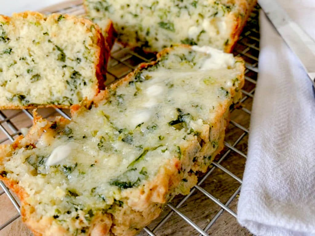 a slice of Spinach Feta Cheese Bread with melted butter