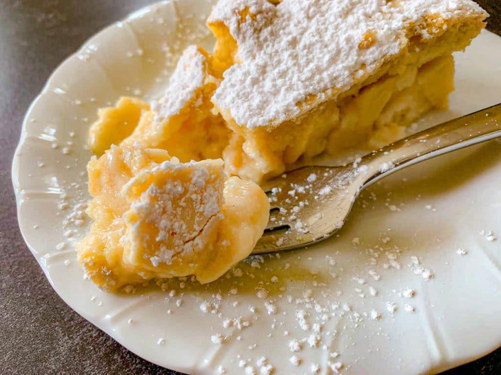 a slice of custard cake on a white plate