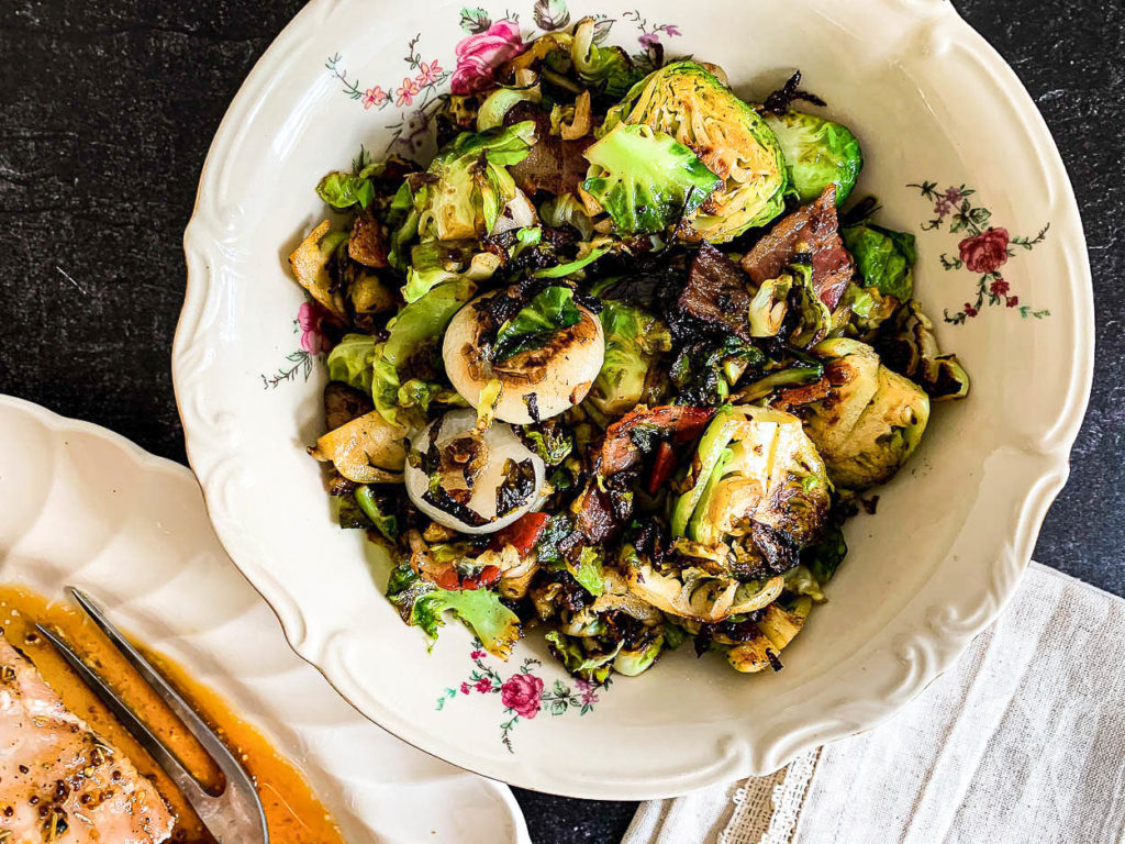 a bowl of Brussels sprouts, with bacon and onions