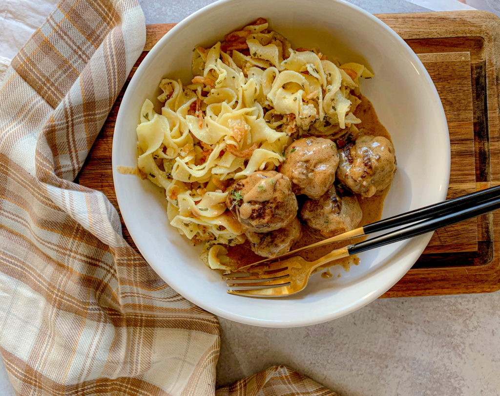 a white bowl with noodles and meatballs