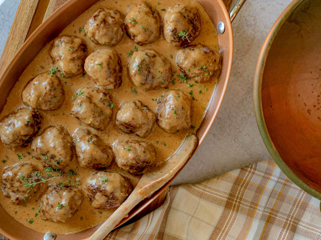a copper chafer with Swedish Meatballs In Creamy Gravy